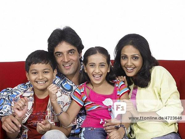 South Asian Indian family with father mother son and daughter sitting on sofa enjoying and looking at camera MR 698   699   700   701