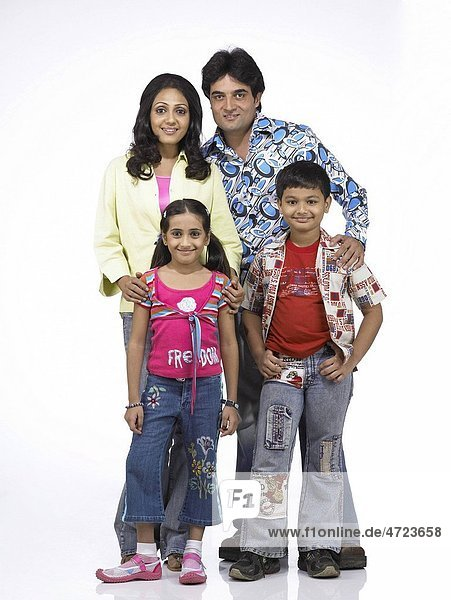 South Asian Indian family with father mother son and daughter standing and looking at camera MR 698   699   700   701