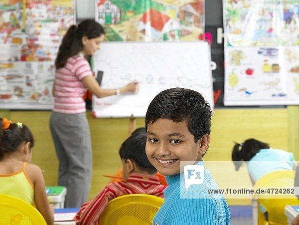 South Asian Indian boy looking behind in nursery school MR