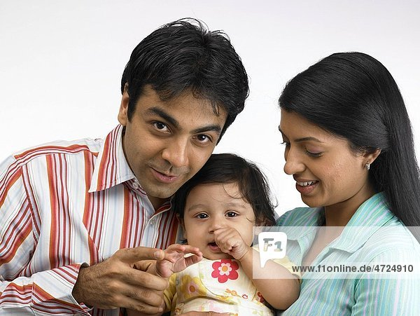 Indian parent with baby girl looking at camera MR702O 702A 702L