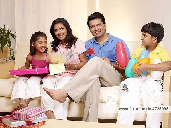 Children and parents with gift boxes balloons sitting in house MR702R MR702S MR702T MR702U