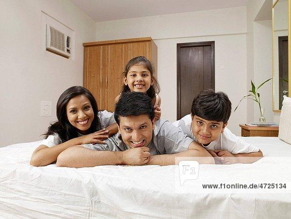 Parents with children lying on bed in bedroom MR702R MR702S MR702T MR702U