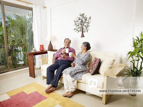 Old couple holding white mugs sitting on sofa MR702T 702S