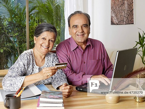 Old couple operating laptop with showing credit card MR702T 702S