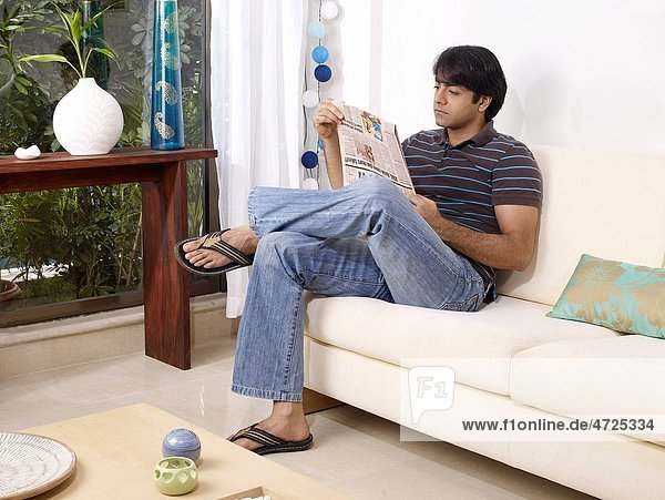 Young man reading newspaper sitting on sofa MR702V