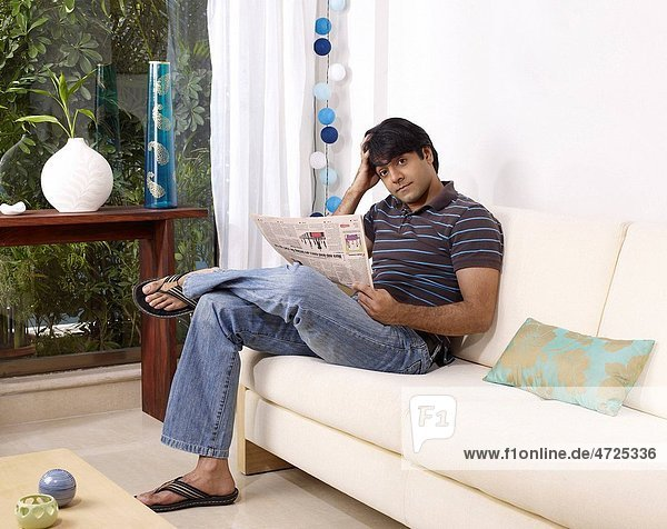 Young man thinking holding newspaper sitting on sofa MR702V