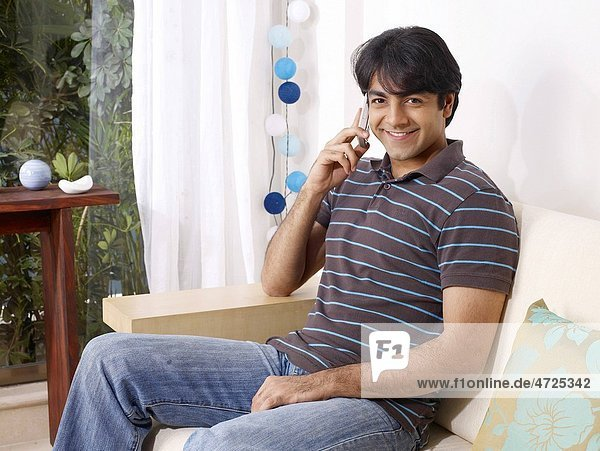 Young man talking on mobile sitting on sofa MR702V