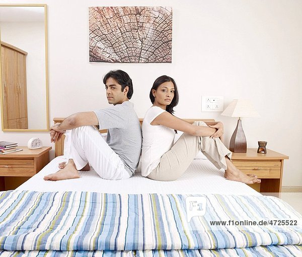 Young man woman sitting back to back on bed MR702V 702U