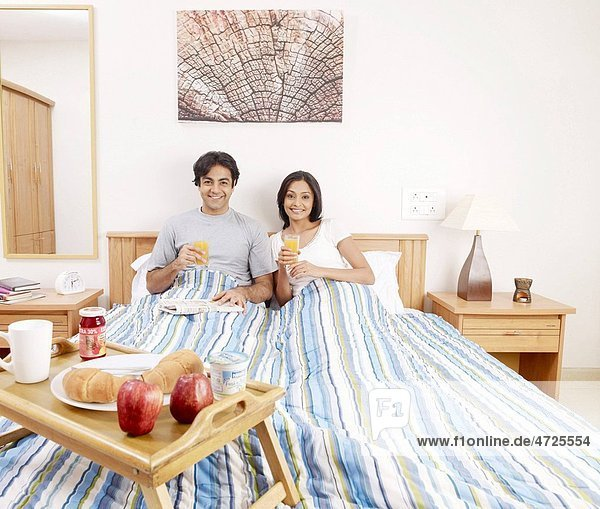 Young man and woman holding juice glasses having breakfast on bed MR702V 702U