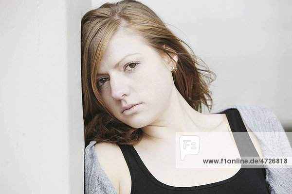 Portrait  junge Frau  lehnt sich an Wand