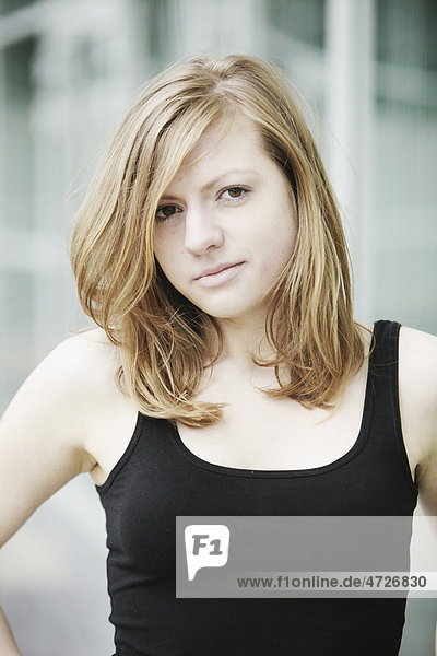 Sensual portrait of a young long-haired woman in a black tank top