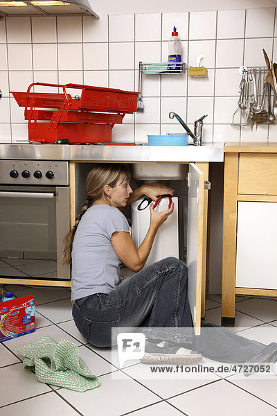Young woman repairing a defective water faucet in a kitchen
