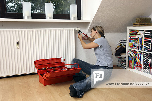 Young woman repairing the thermostat of a radiator