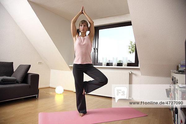 Junge Frau macht zu Hause Yoga