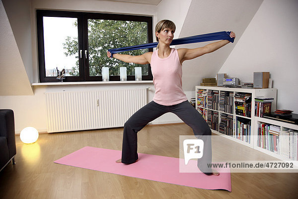 Young woman exercising with a resistance band  Deuser band  at home