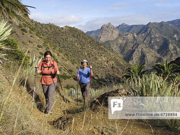 Mann und Frau mit Wanderstöcken wandern im Barranco de la Era Nueva  hinten Roque Cano  Vallehermoso  La Gomera  Kanaren  Spanien  Europa