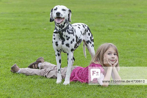 Little girl lying under a Dalmatian