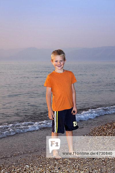 Boy  7  in the evening on a pebble beach  Corfu  Ionian Islands  Greece  Southern Europe  Europe