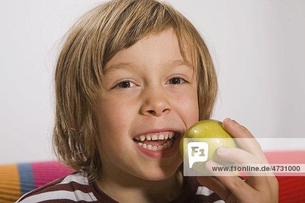 Junge  6 Jahre  isst eine Birne