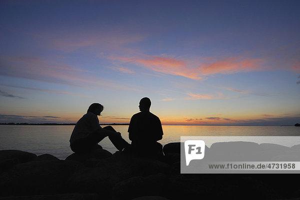 Silhouette eines Paares an einem See bei Sonnenuntergang  Schweden  Europa