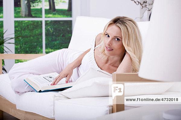 Junge Frau liest auf dem Sofa