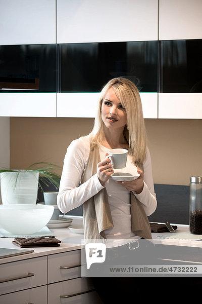 Junge Frau mit Kaffeetasse in der Küche
