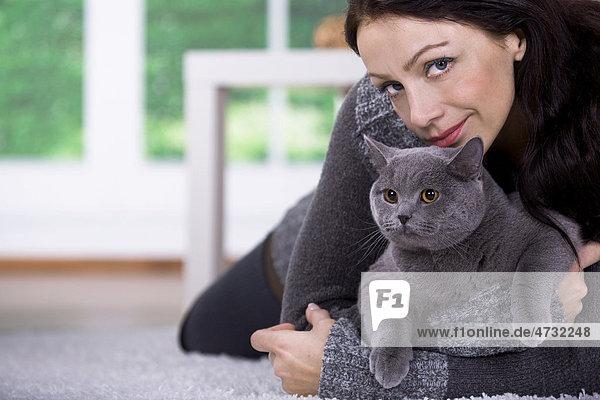 Junge Frau zu Hause mit einer Britischen Kurzhaar-Katze