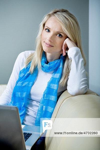 Eine junge Frau mit einem Laptop auf dem Sofa