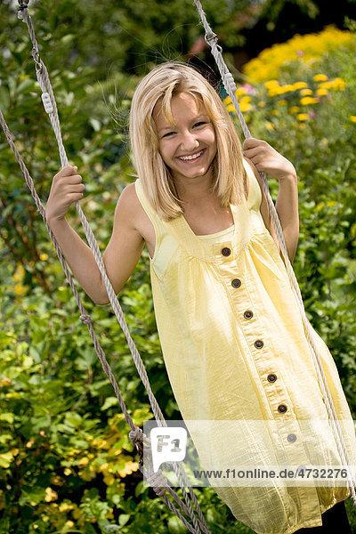 Mädchen  Teenager  auf einer Schaukel im Garten