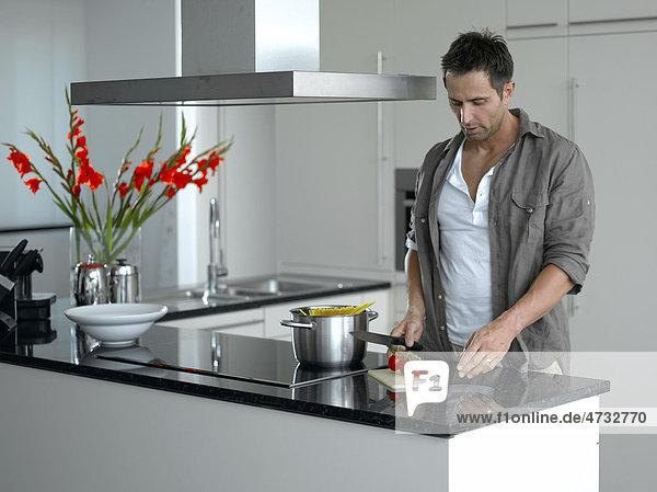 Mann in moderner Küche beim Tomaten schneiden