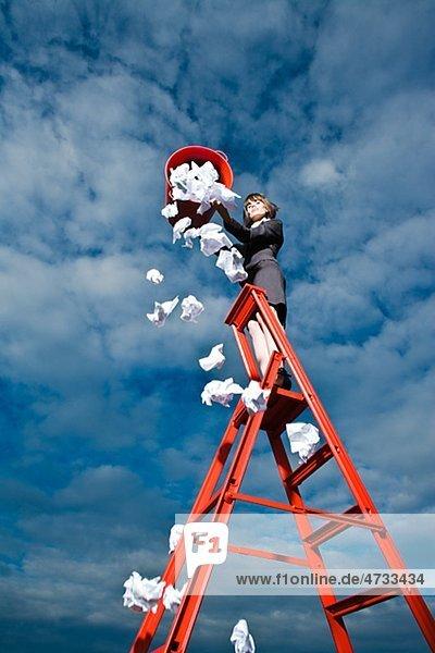 Frau von red bin stehend auf Leiter Müll werfen