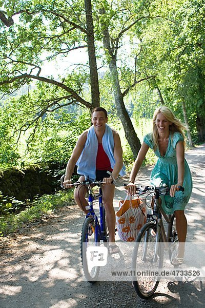 Junges paar Radfahren auf unbefestigten Weg durch Wald