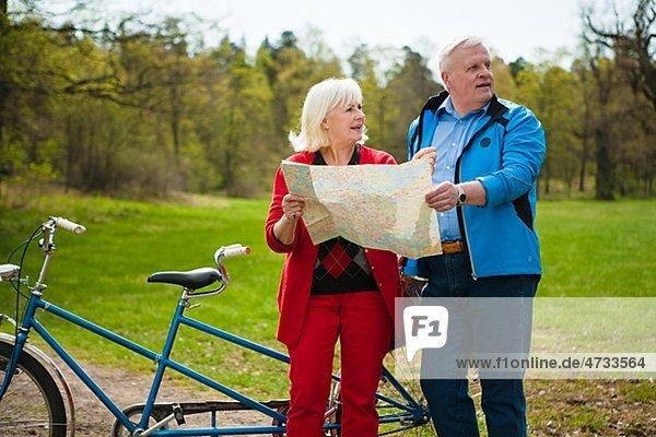 älteres Paar mit Tandem-Fahrrad