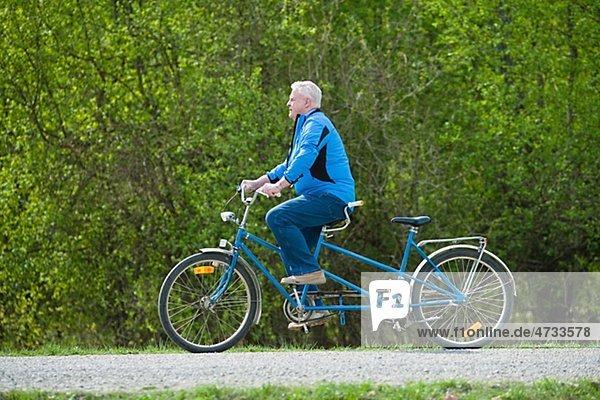 älterer Mann auf Tandem-Fahrrad