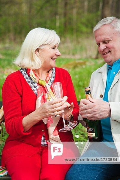 älteres Paar öffnen Weinflasche im park