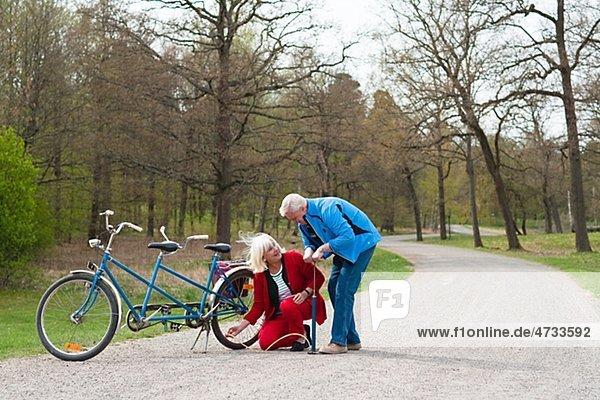 älteres Paar fixieren Tandem-Fahrrad im park