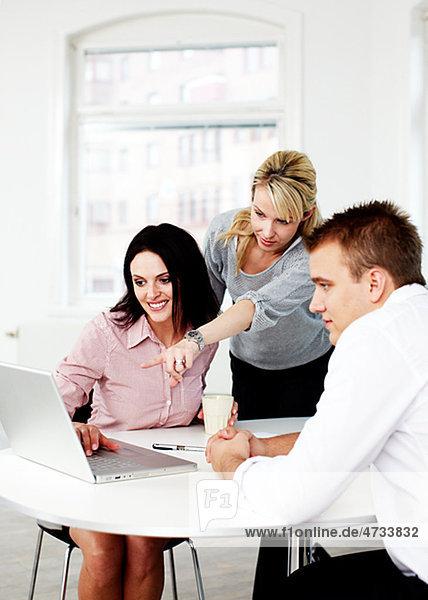 Geschäftsleute betrachten Laptop im Büro