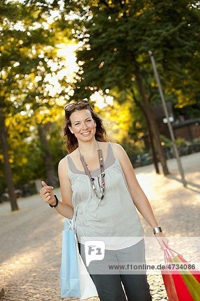 Lächelnde Frau zu Fuß auf der Straße mit der hält Einkaufstaschen