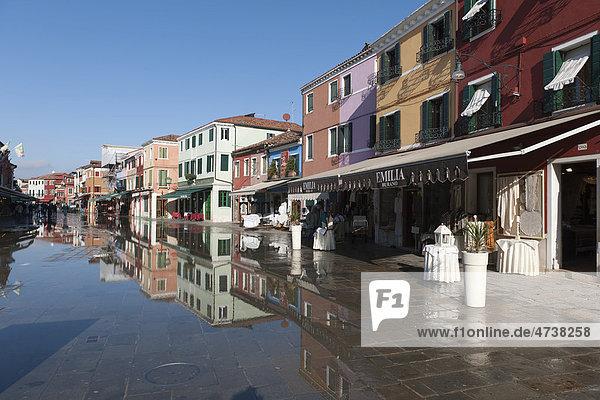 Das winterliche Hochwasser  aqua alta  überspült die Haupteinkaufsstraße  die Häuser spiegeln sich im Wasser  Insel Burano  Venedig  Italien  Südeuropa