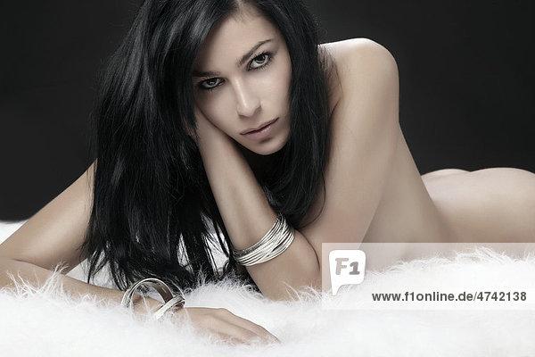 Auf einem weißen Fell liegende nackte junge Frau  Beauty Auf einem weißen Fell liegende nackte junge Frau, Beauty