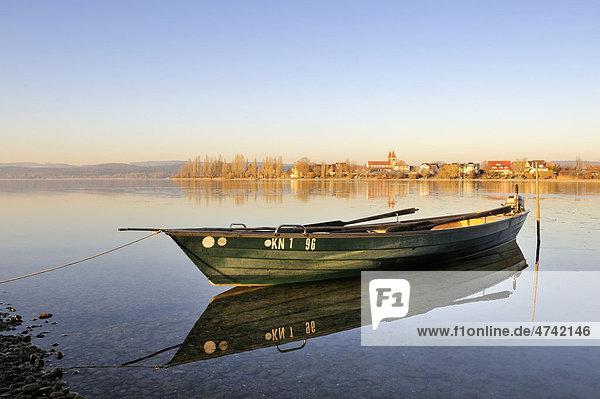 Abendstimmung mit Fischerboot am Ufer der Insel Reichenau  dahinter die Kirche St  Peter und Paul auf dem Inselteil Niederzell  Landkreis Konstanz  Baden-Württemberg  Deutschland  Europa