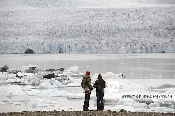 Touristen bewundern die Eisberge die in der Gletscherlagune Brei_alÛn treiben  Südisland  Island  Europa