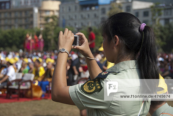 Police officer in uniform photographing at an ethnic festival  Jiangcheng  Pu'er City  Yunnan Province  People's Republic of China  Southeast Asia  Asia