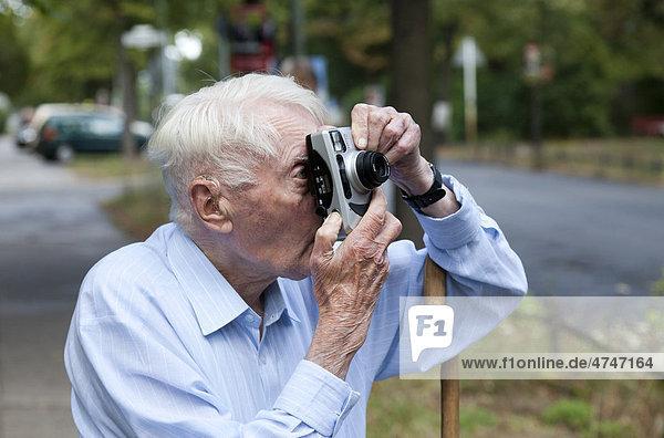 Senior citizen looking through a camera  taking photos