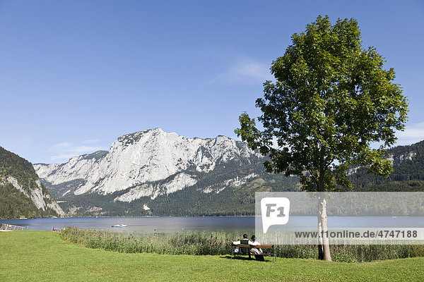Young couple wearing traditional costume sitting on a park bench at Altausee Lake  Salkkammergut  Austria  Europe