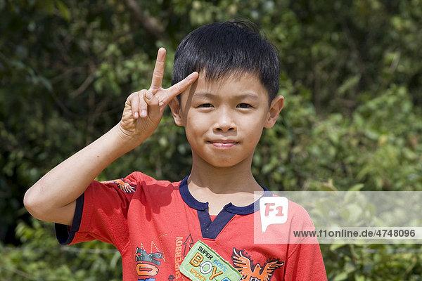 Vietnamesischer Junge mit Victory-Zeichen  auf der Insel Phu Quoc  Vietnam  Südostasien Vietnamesischer Junge mit Victory-Zeichen, auf der Insel Phu Quoc, Vietnam, Südostasien