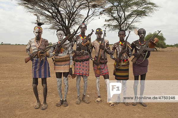 Group of Karo warriors with body and facial paintings holding a rifle over their shoulder  Omo river valley  Southern Ethiopia  Africa