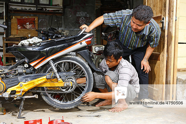Young men repairing a motorcycle during a mechanics apprenticeship  vocational training center  Siantar  Sumatra  Indonesia  Asia