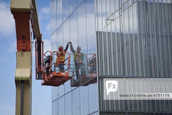 Männlich Glazer installiert Glas FOM ein Mann den Auftrieb an der Außenseite des Anchorage Museum zusätzlich während der Bauphase  Anchorage  Südalaska  Frühling