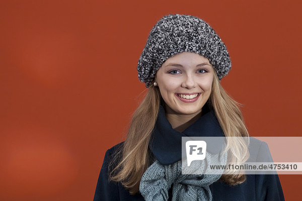 Smiling young woman with hat  scarf and winter coat